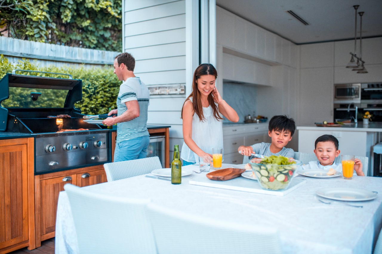 Family with two children having lunch outdoors. They are enjoying time together. Father is using barbecue grill.