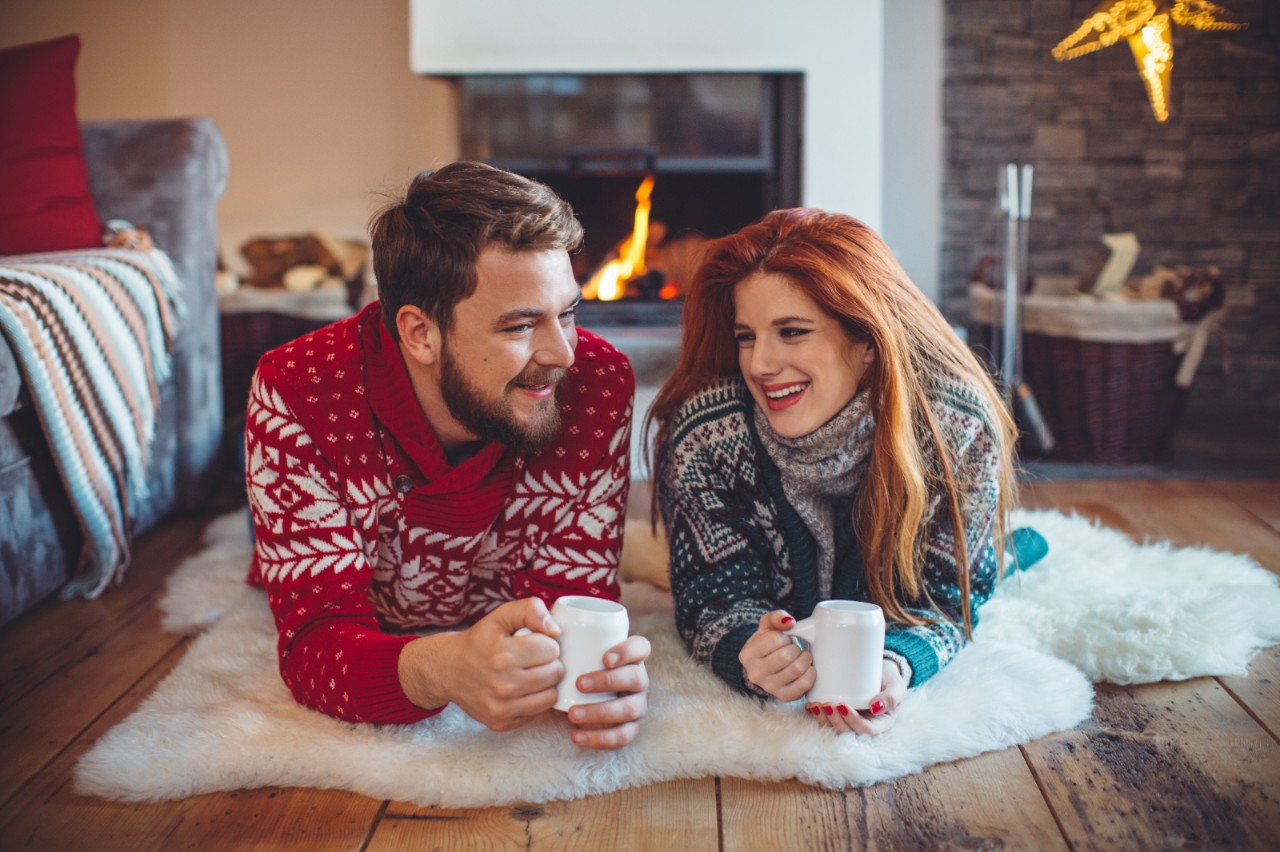 Couple on vacation at mountain cabin. Lying on the floor on a blanket and drinking hot drink by a fireplace in a cozy  living room on Christmas. Wearing festive knitted sweaters. Austrian Alps.